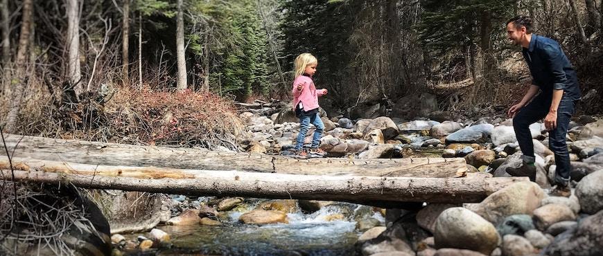 enfant qui traverse un ruisseau sur un tronc